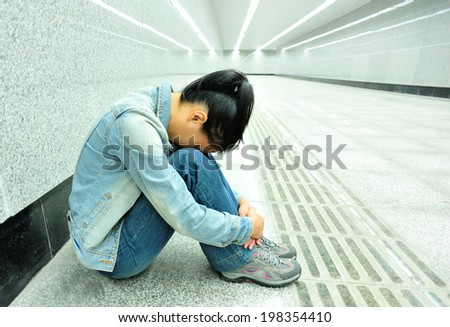 disappointed woman sit on the passage of subway station - stock photo