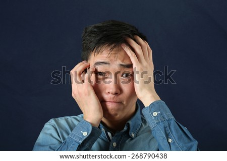 Disappointed young Asian man looking at camera - stock photo