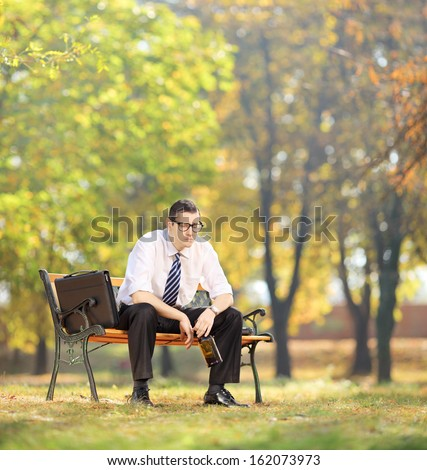 Disappointed young businessman sitting on a wooden bench with bottle in his hand, in park, shot with tilt and shift