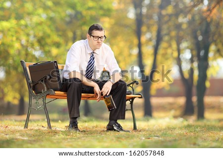 Disappointed young businessperson sitting on a wooden bench with bottle in his hand, in a park - stock photo