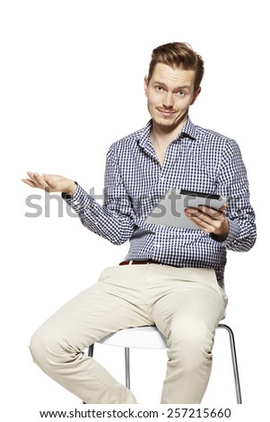 Disappointed young man holding tablet. Studio shot isolated on white. - stock photo