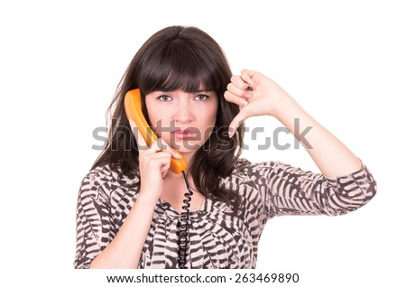 disappointed young woman using retro orange telephone holding thumb down isolated on white - stock photo
