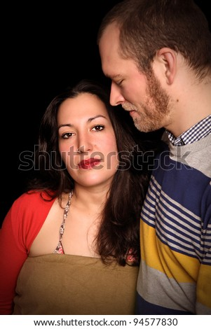 disappointment. young couple in front of black background with serious expression - stock photo