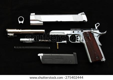 Disassembled handgun on black background, Seperate parts handgun. Pistol Part. - stock photo