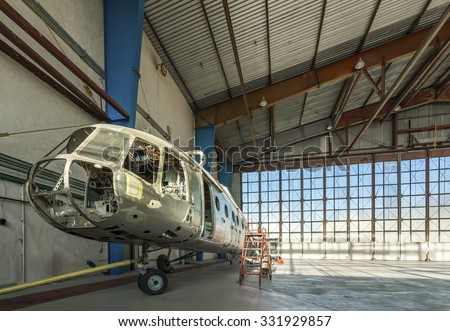 Disassembled helicopter in repair stand in the air hangar. Aircraft without internal details, seats and trim.