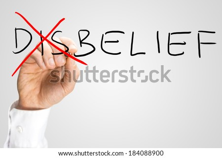 Disbelief - Belief, a concept of opposites with a man crossing through the Dis of the handwritten word Disbelief on a virtual screen with copyspace. - stock photo