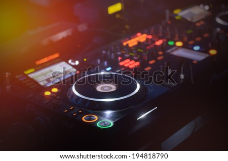 Disc Jockey mixing deck and turntables at night with colourful illuminated controls for mixing music for a party or disco - stock photo