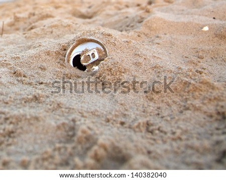 Discarded aluminum can in the sand - sea and beach  - stock photo