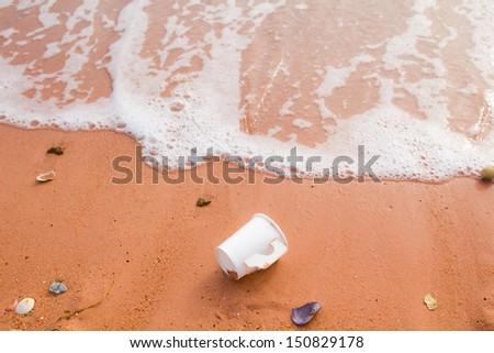 Discarded paper cup in the sand - stock photo