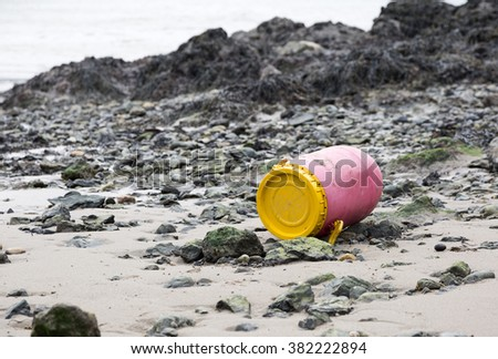 Discarded plastic barrel on rocky beach - stock photo