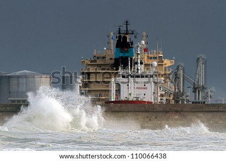 Discharge of hazardous and flammable materials in the port of Leixoes in a stormy day - stock photo