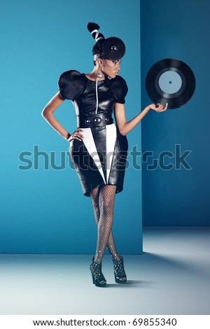 Disco african women stands with vinyl record in her hand - stock photo