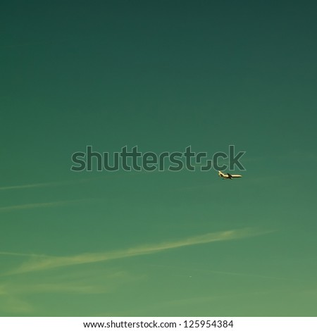 Discolored image showing a plane flying high in the sky. - stock photo