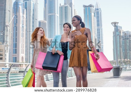 Discounts. Beautiful girl in dress holding shopping bags in their hands on the embankment among the skyscrapers while walking down the street with shopping bags - stock photo