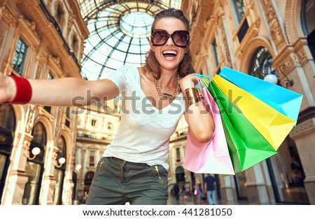 Discover most unexpected trends in Milan. Smiling fashion woman in eyeglasses with colorful shopping bags taking selfie in Galleria Vittorio Emanuele II