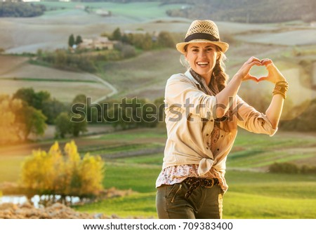 Discovering magical views of Tuscany. happy healthy woman hiker in hat in Tuscany showing heart shaped hands