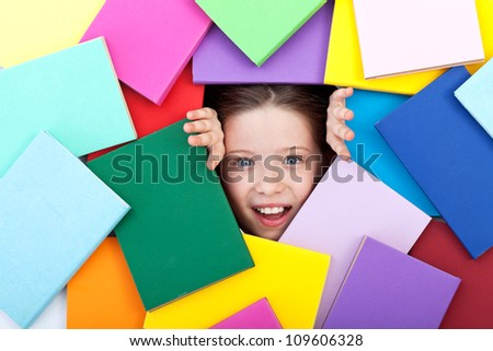 Discovering the wonderful world of knowledge - amazed young girl emerging from beneath colorful books - stock photo