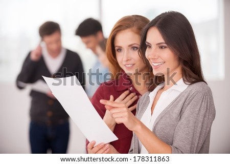 Discussing a good condition contract. Two beautiful young women discussing document while two men communicating on background