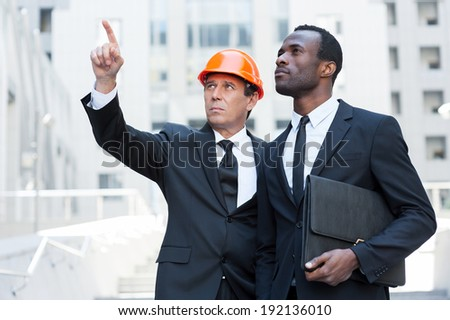 Discussing building project. Confident contractor in hardhat pointing away while standing together with African businessman - stock photo