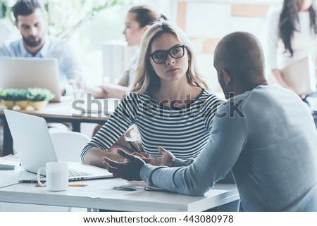 Discussing business. Two young business people discussing something while sitting at the office desk together while their colleagues sitting in the background - stock photo
