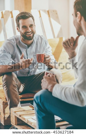 Discussing business. Two young men holding cups of coffee and discuss something while sitting in the rest area of the office - stock photo