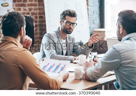 Discussing business. Young handsome man in eyeglasses gesturing and discussing something while his coworkers while sitting at the office table together - stock photo