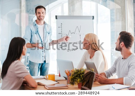 Discussing company progress. Confident young man standing near whiteboard and pointing graph while his colleagues sitting at the desk  - stock photo