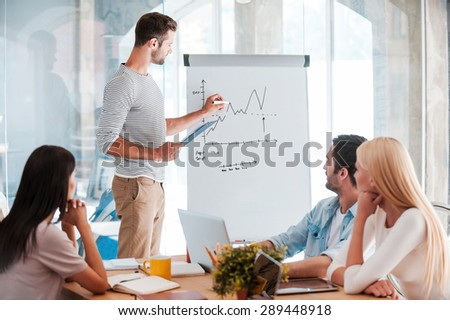 Discussing company progress. Confident young man standing near whiteboard and sketching while his colleagues sitting at the desk  - stock photo