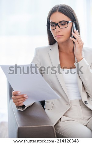 Discussing contract. Confident young businesswoman in suit examining document and talking on the mobile phone while sitting at the chair - stock photo