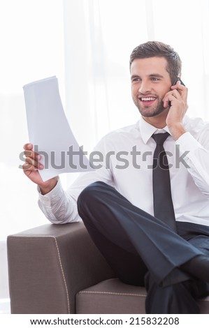 Discussing contract. Happy young businessman in shirt and tie talking on the mobile phone and holding document while sitting at the chair - stock photo