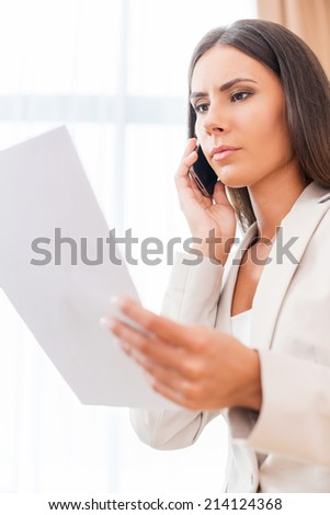 Discussing contract. Low angle view of confident young businesswoman in suit talking on the mobile phone and holding document