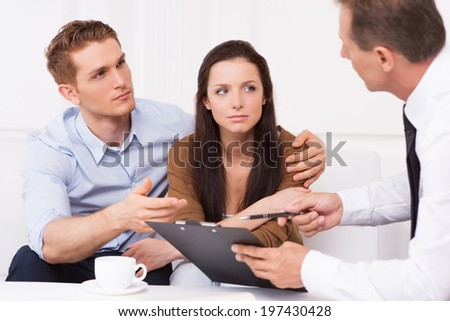 Discussing contract. Thoughtful young couple sitting on the couch while man in formalwear explaining something and pointing clipboard - stock photo