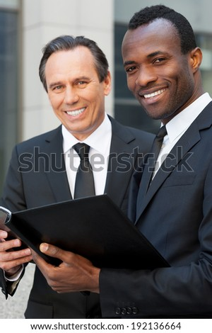 Discussing contract together. Two cheerful business men holding note pad and looking at camera while standing outdoors - stock photo