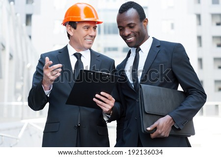 Discussing new building project. Cheerful contractor in hardhat gesturing and and smiling while standing together with African businessman - stock photo