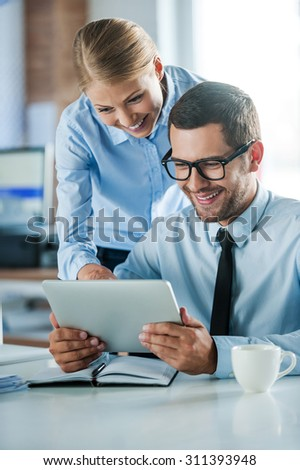 Discussing new business project. Two happy young people in formalwear smiling and looking at digital tablet while working together  - stock photo