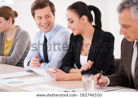 Discussing project together. Confident business people sitting in a row at the table while man and woman in formalwear talking to each other and smiling