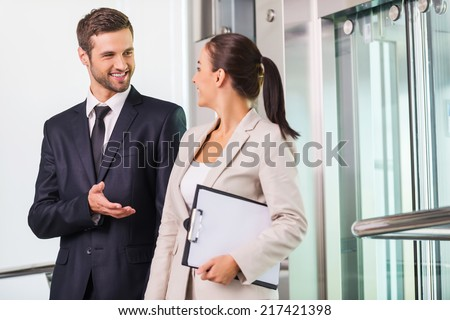 Discussing project with colleague. Two cheerful business people discussing something and smiling while getting out from elevator  - stock photo