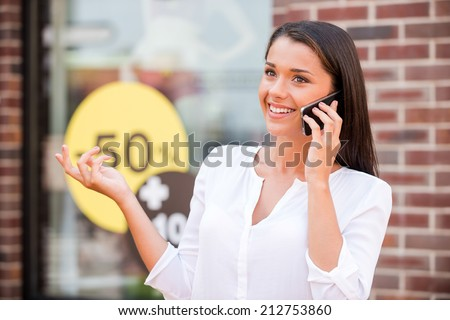 Discussing sale. Beautiful young woman talking on the phone and smiling while standing against clothing store  - stock photo