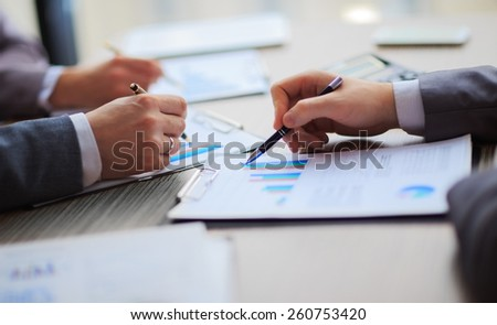 Discussing the scheme. Side view of business people, pointing handles on the chart together, sitting at the table - stock photo