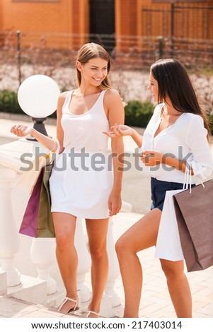 Discussing their day shopping. Two beautiful young women with shopping bags walking together and talking - stock photo