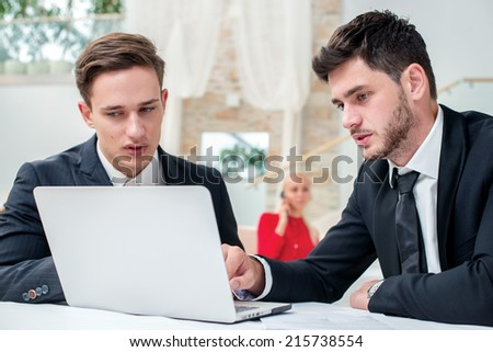 Discussion of business. Two successful and confident businessman sitting at the table in a business office in full costume in the office and working at a laptop and looking at laptop - stock photo