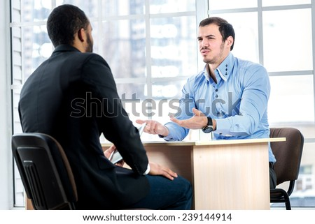 Discussion of the proposal. Businessman swings his arms while two successful businessman sitting at the table against each in the business office in formal wear and work at a laptop. - stock photo