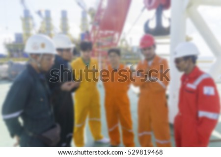 Discussion session. Men with coveralls discussing on site. Motion blur effect.
