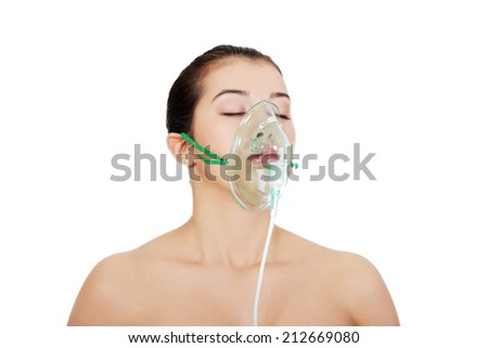 Diseased female patient wearing a oxygen mask against white background