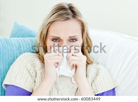 Diseased woman using a tissue sitting on a sofa at home