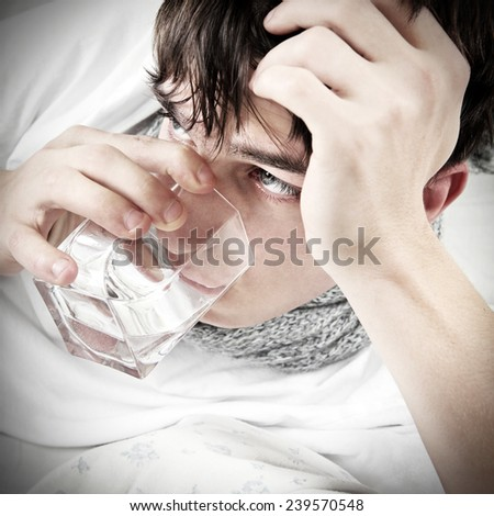 Diseased Young Man drink the water on the Bed closeup - stock photo
