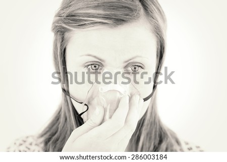 Diseased young woman wearing a mask against white background - stock photo