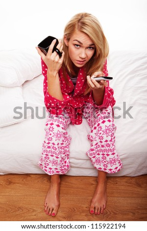 Disgruntled young woman in her pyjamas sitting on the edge of her bed changing TV channels - stock photo