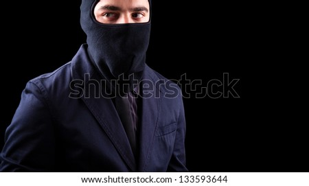 Disguise thief against black background - stock photo