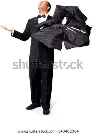 Disgusted African man with short black hair in evening outfit holding umbrella - Isolated